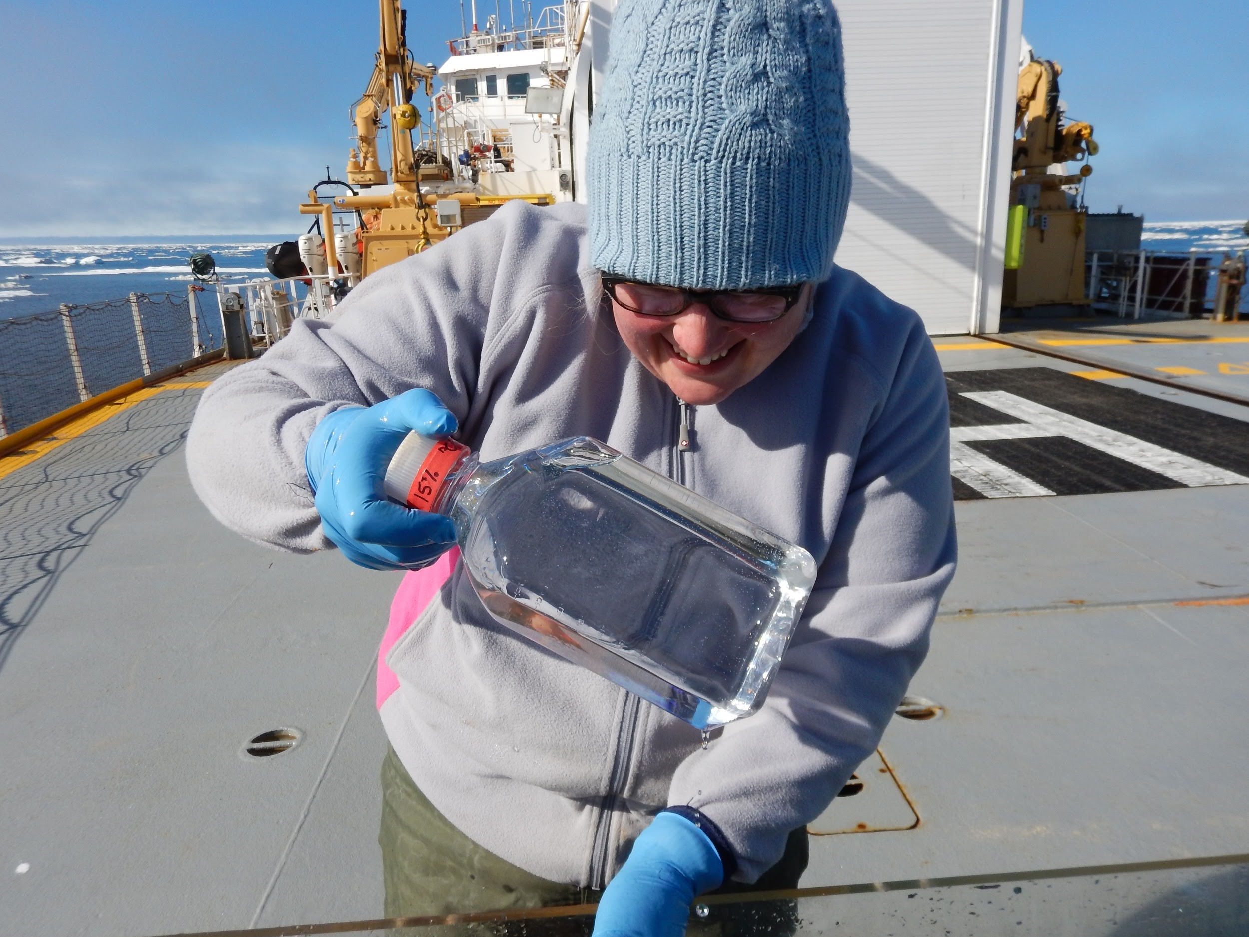 Karina holding a water sample collected on the CCGS Sir Wilfred Laurier during a research cruise in the Arctic. The cruise was conducted as part of the Distributed Biological Observatory (DBO) program