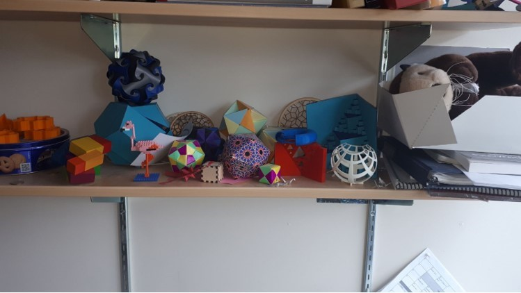 Dina's collection of math and art objects that she uses to help communicate different mathematical ideas, stored on her bookshelf at UVic (not all created by her)