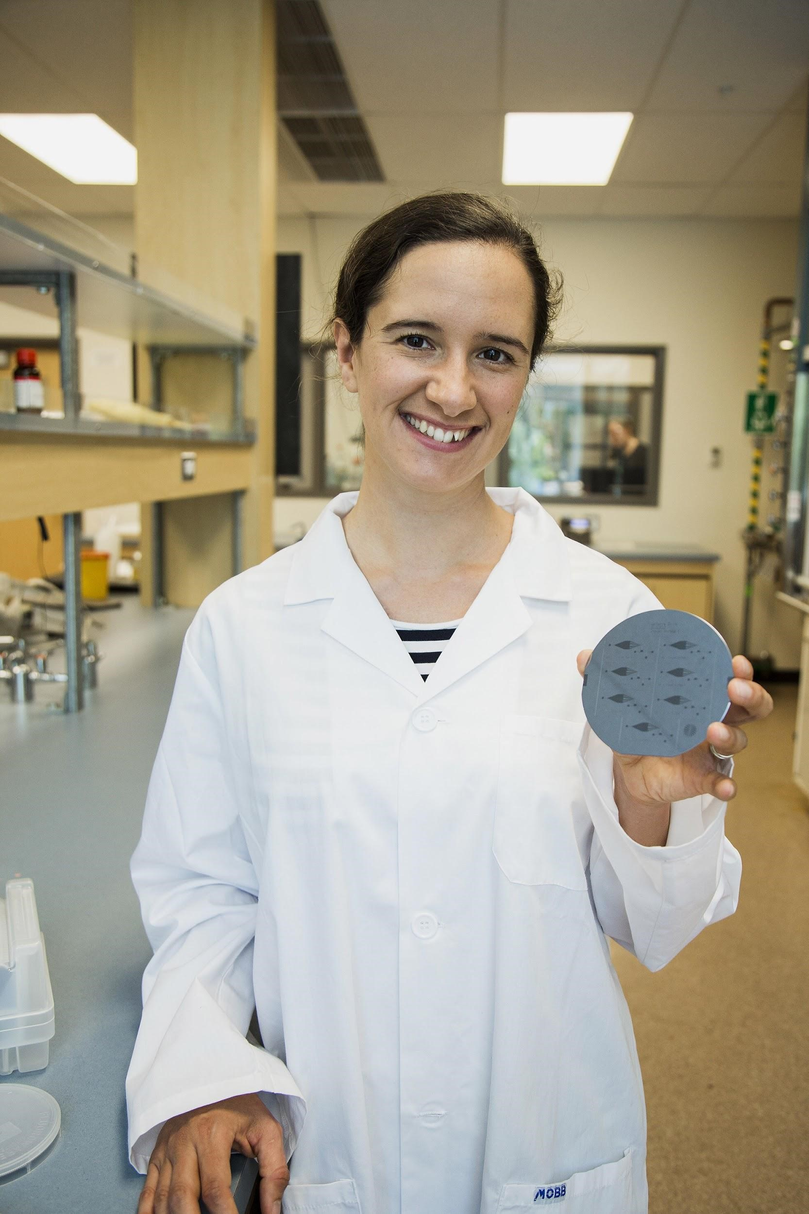 Katherine holding a microfluidic (lab-on-a-chip) device produced in her lab