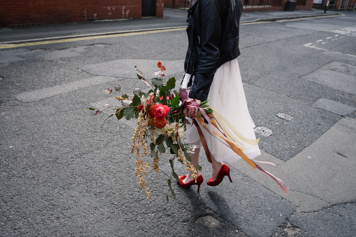 The sunlight shines on Martha as she carries her wedding bouquet by Florist Fletcher and Foley. Martha wears red shoes