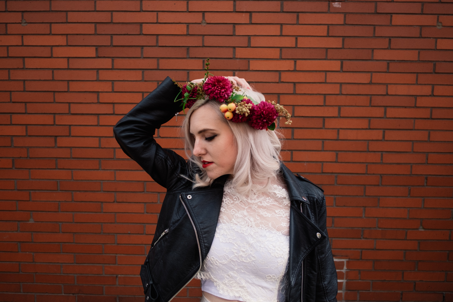 Martha wears flower crown by Fletcher and Foley, leather jacket and Wilderness Bride dress in Manchester Northern Quarter