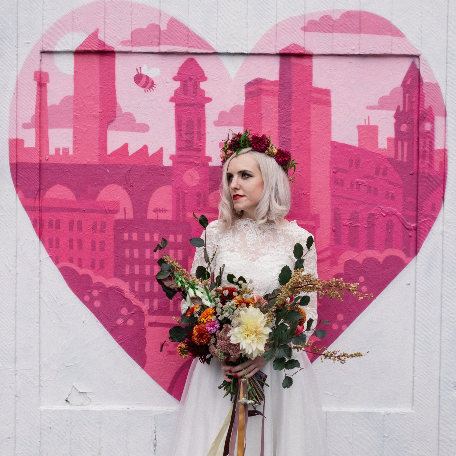 Martha is stood outside the outhouse in Manchester Northern Quarter, it is decorated with a pink heart and the sky line of Manchester