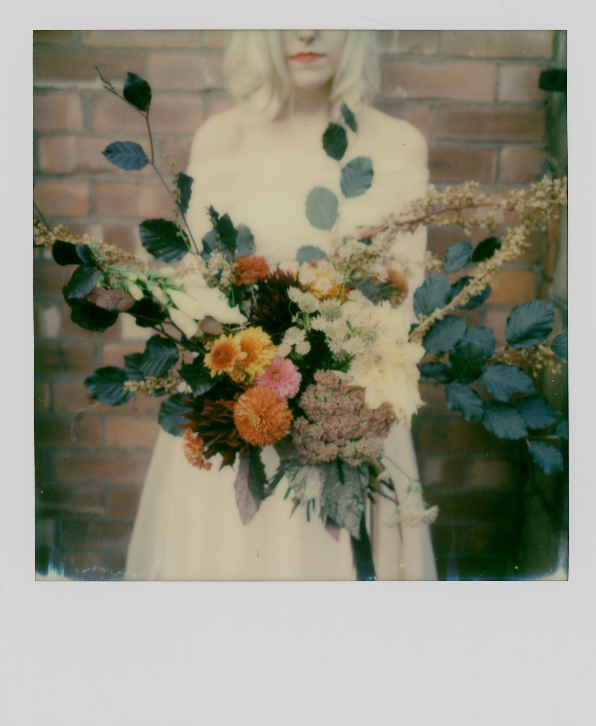 Colour SX70 Polaroid of Martha with her Autumnal bouquet held face on. Martha wears Wilderness Bride indie wedding dress