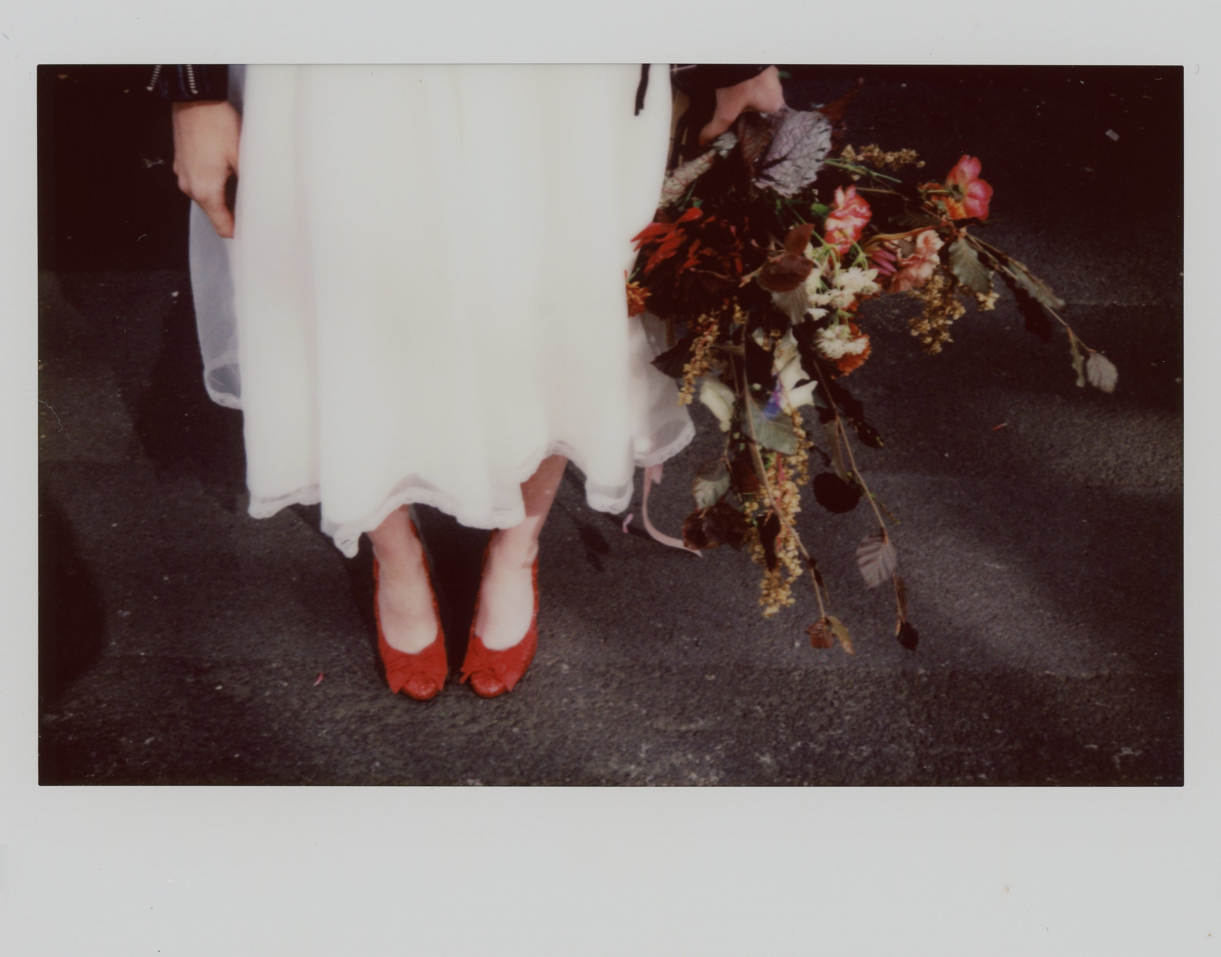 Instax wide photograph of Martha bending down to tie her florence shoes, outside Manchester Soup Kitchen in the Northern Quarter
