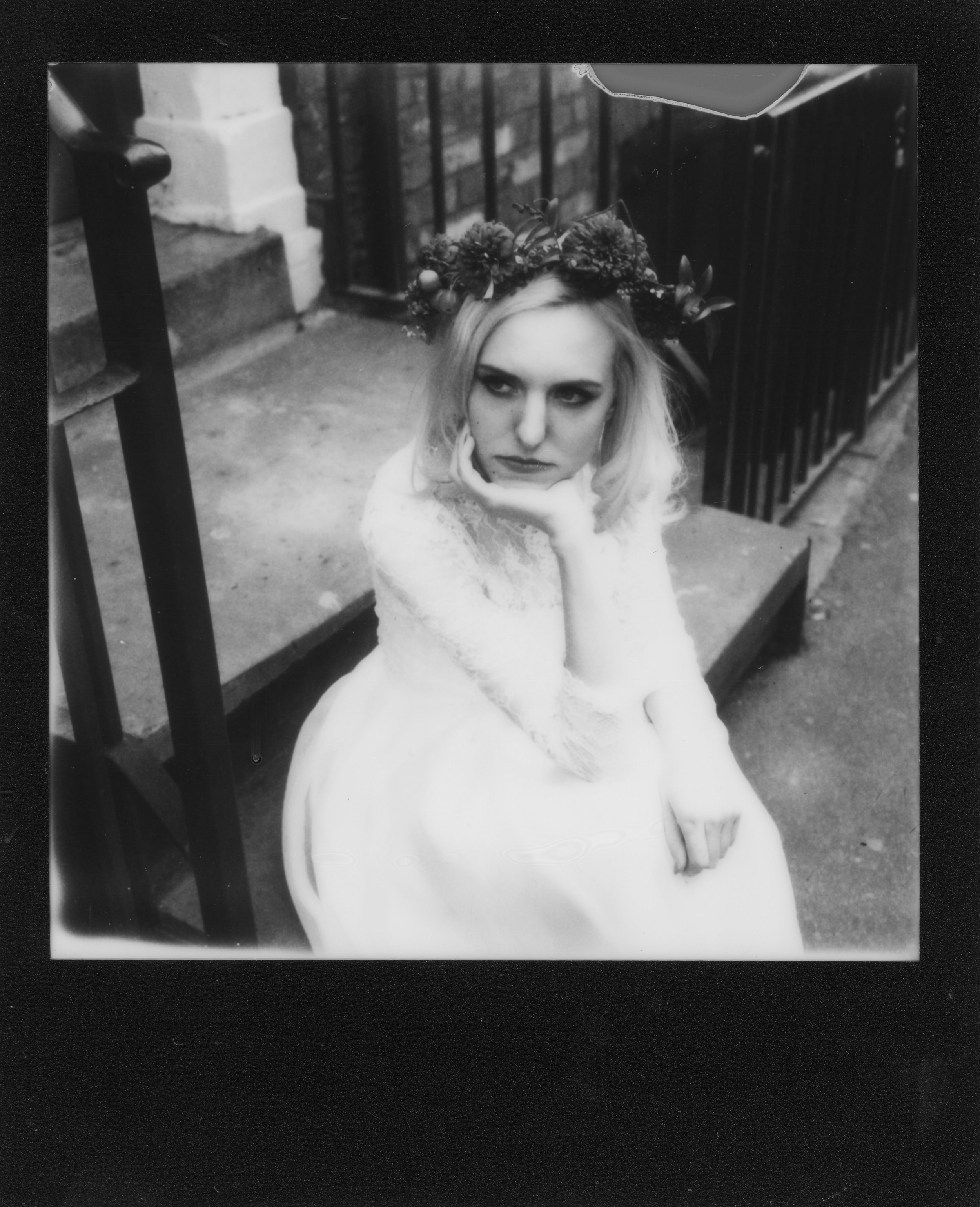 Black and white Polaroid of Martha sat down in a Wilderness Bride wedding dress in Manchester