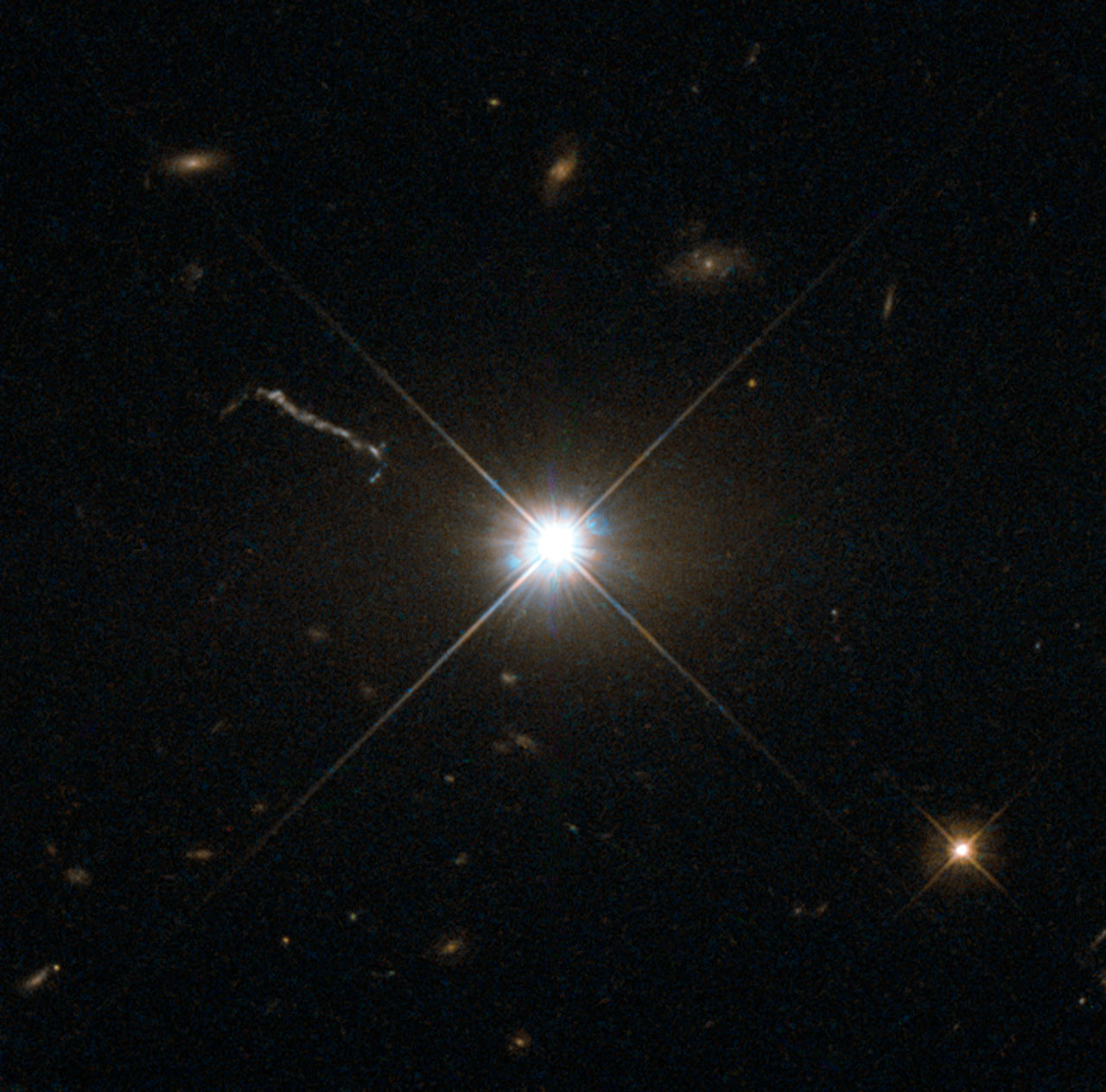 """Figure 3: """"This image from Hubble's Wide Field and Planetary Camera 2 (WFPC2) is likely the best of ancient and brilliant quasar 3C 273, which resides in a giant elliptical galaxy in the constellation of Virgo (The Virgin). Its light has taken some 2.5 billion years to reach us. Despite this great distance, it is still one of the closest quasars to our home. It was the first quasar ever to be identified, and was discovered in the early 1960s by astronomer Allan Sandage. The term quasar is an abbreviation of the phrase """"quasi-stellar radio source"""", as they appear to be star-like on the sky. In fact, quasars are the intensely powerful centres of distant, active galaxies, powered by a huge disc of particles surrounding a supermassive black hole. As material from this disc falls inwards, some quasars — including 3C 273 — have been observed to fire off super-fast jets into the surrounding space. In this picture, one of these jets appears as a cloudy streak, measuring some 200 000 light-years in length. Quasars are capable of emitting hundreds or even thousands of times the entire energy output of our galaxy, making them some of the most luminous and energetic objects in the entire Universe. Of these very bright objects, 3C 273 is the brightest in our skies. If it was located 30 light-years from our own planet — roughly seven times the distance between Earth and Proxima Centauri, the nearest star to us after the Sun — it would still appear as bright as the Sun in the sky. WFPC2 was installed on Hubble during shuttle mission STS-125. It is the size of a small piano and was capable of seeing images in the visible, near-ultraviolet, and near-infrared parts of the spectrum.""""\(^{[3]}\)  Image Credit:ESA/Hubble [CC BY 4.0 (http://creativecommons.org/licenses/by/4.0)], via Wikimedia Commons"""