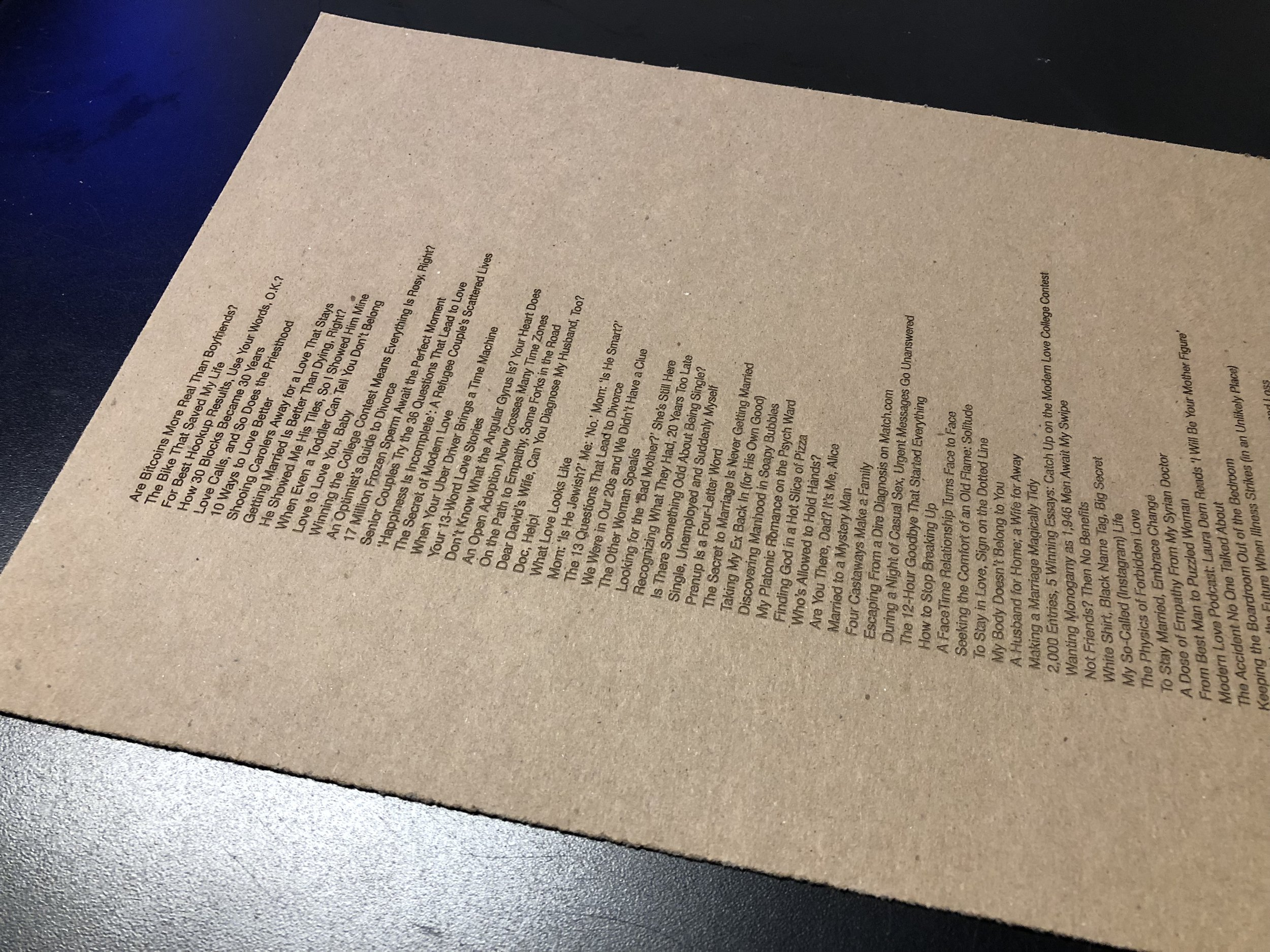 Real Modern Love headlines laser-printed on cardboard as an artifact of real stories told via the NY Times.