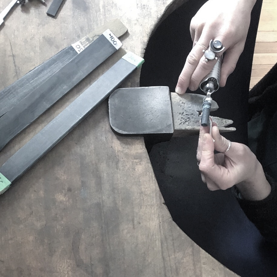 Working at jewellery bench with tools