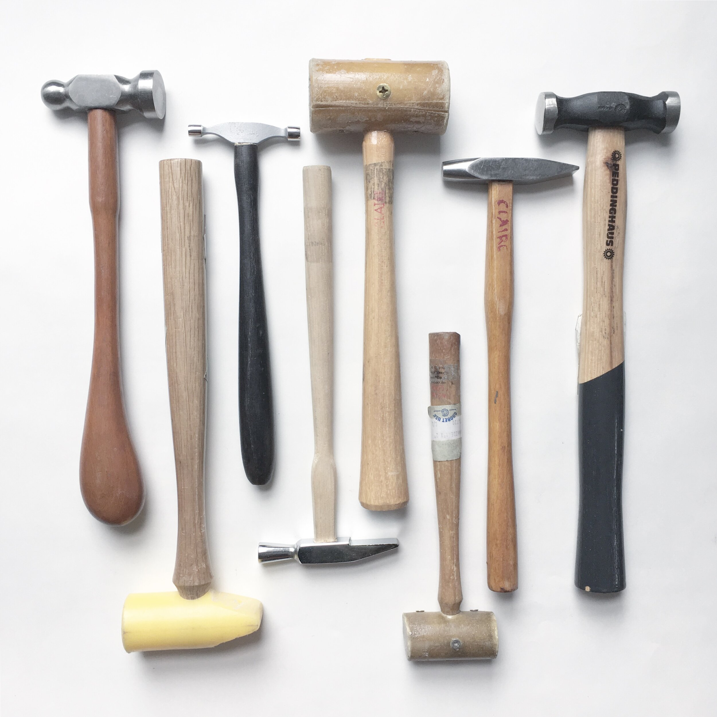 A variety of different hammers used to manipulate metal.