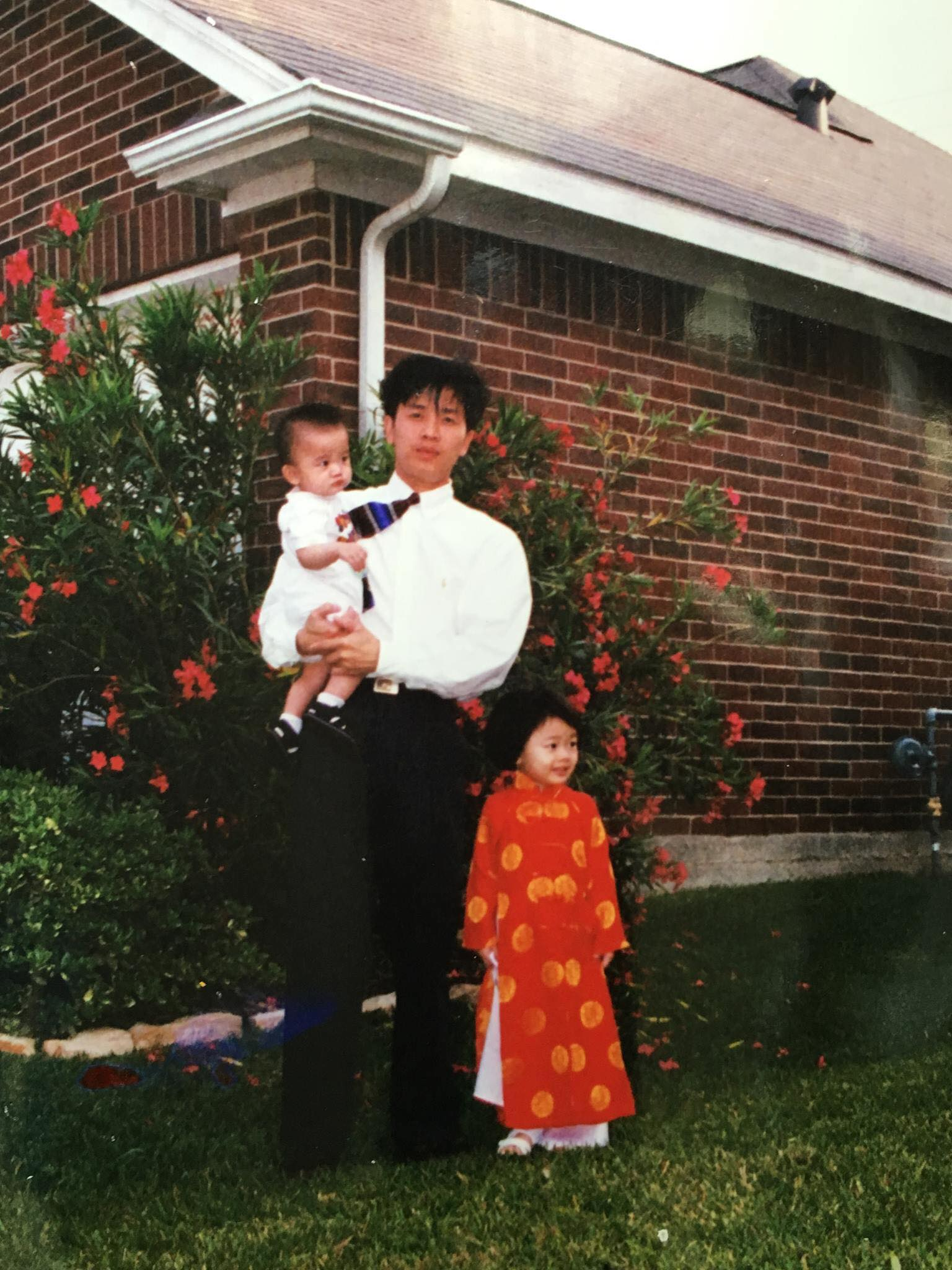 The author in a red áo dài with her father holding her baby brother.