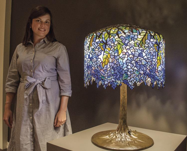 Sally Meyer, adult programs manager at the Museum of the Shenandoah Valley, stands with a Tiffany lamp designed by Clara Driscoll, called Wisteria, which contains 2,000 pieces of glass.  Jenny Baker/The Winchester Star