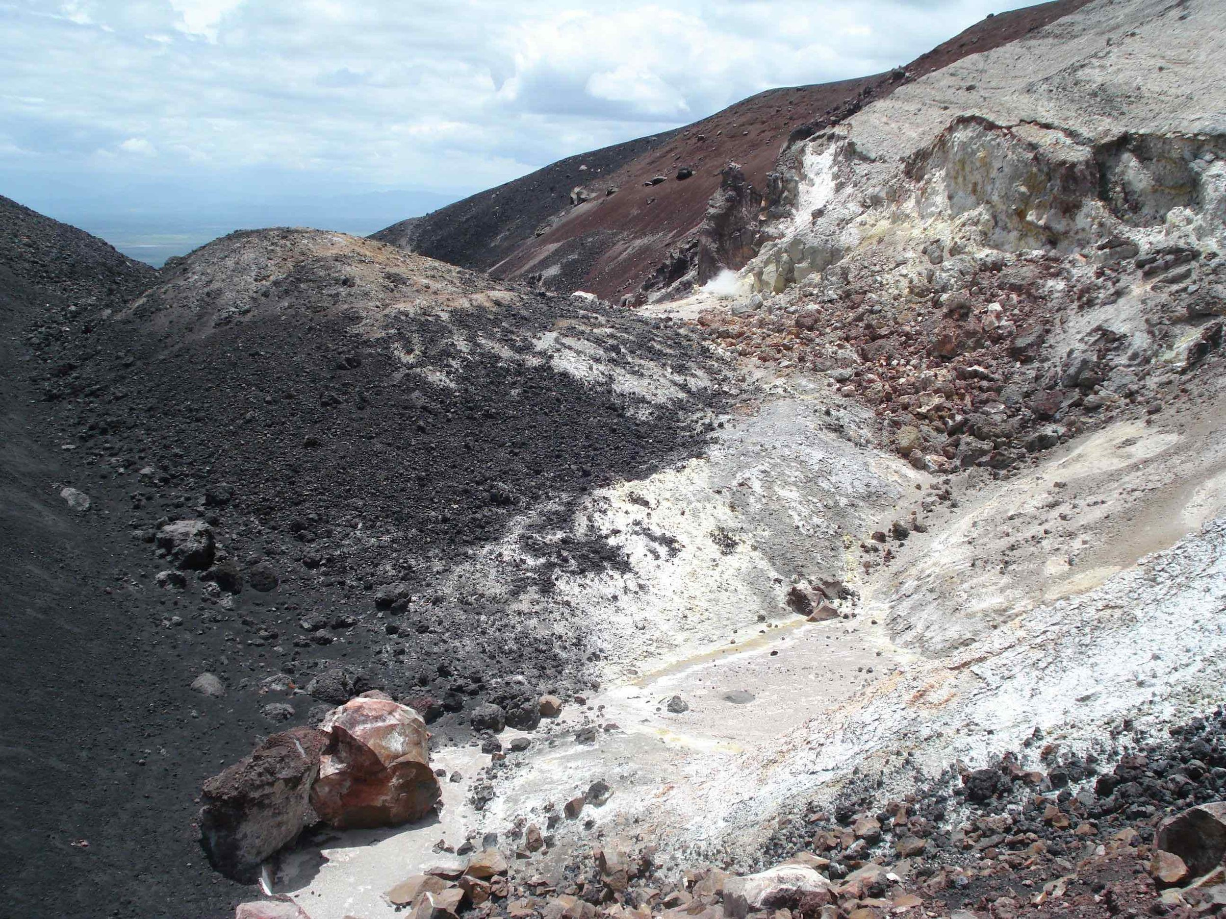 To the left is the fresh black basalt of the current cone. The light area on the right is the highly weathered inside flank of an older eruption cone. The flat middle area (pinkish) is an outwash basin or drainage area.
