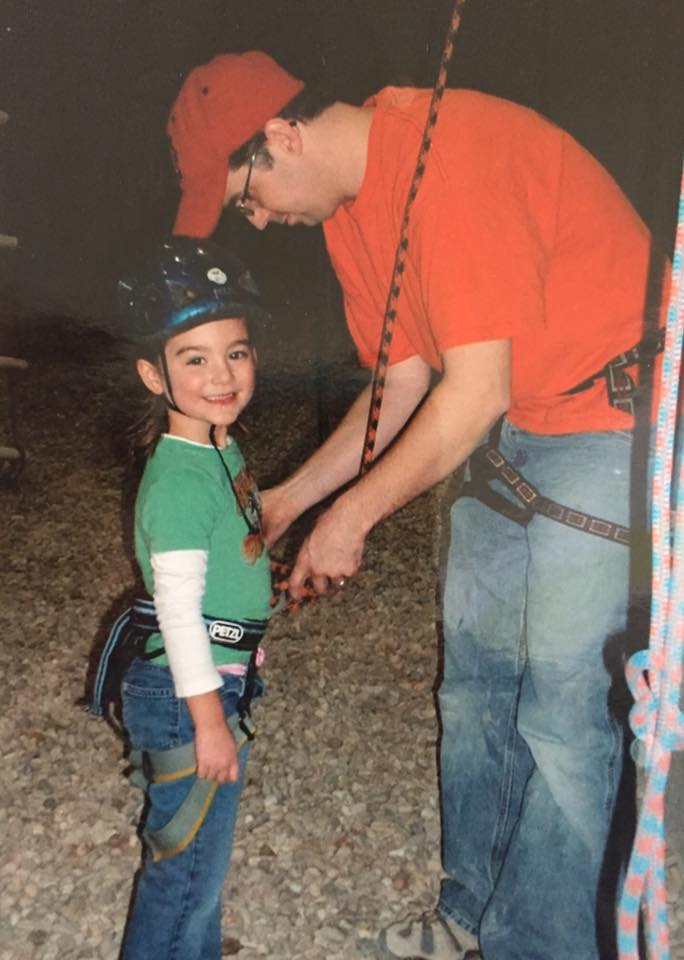 Jr. Team Coach Jim Bell helping a new climber at a birthday party in 2006.