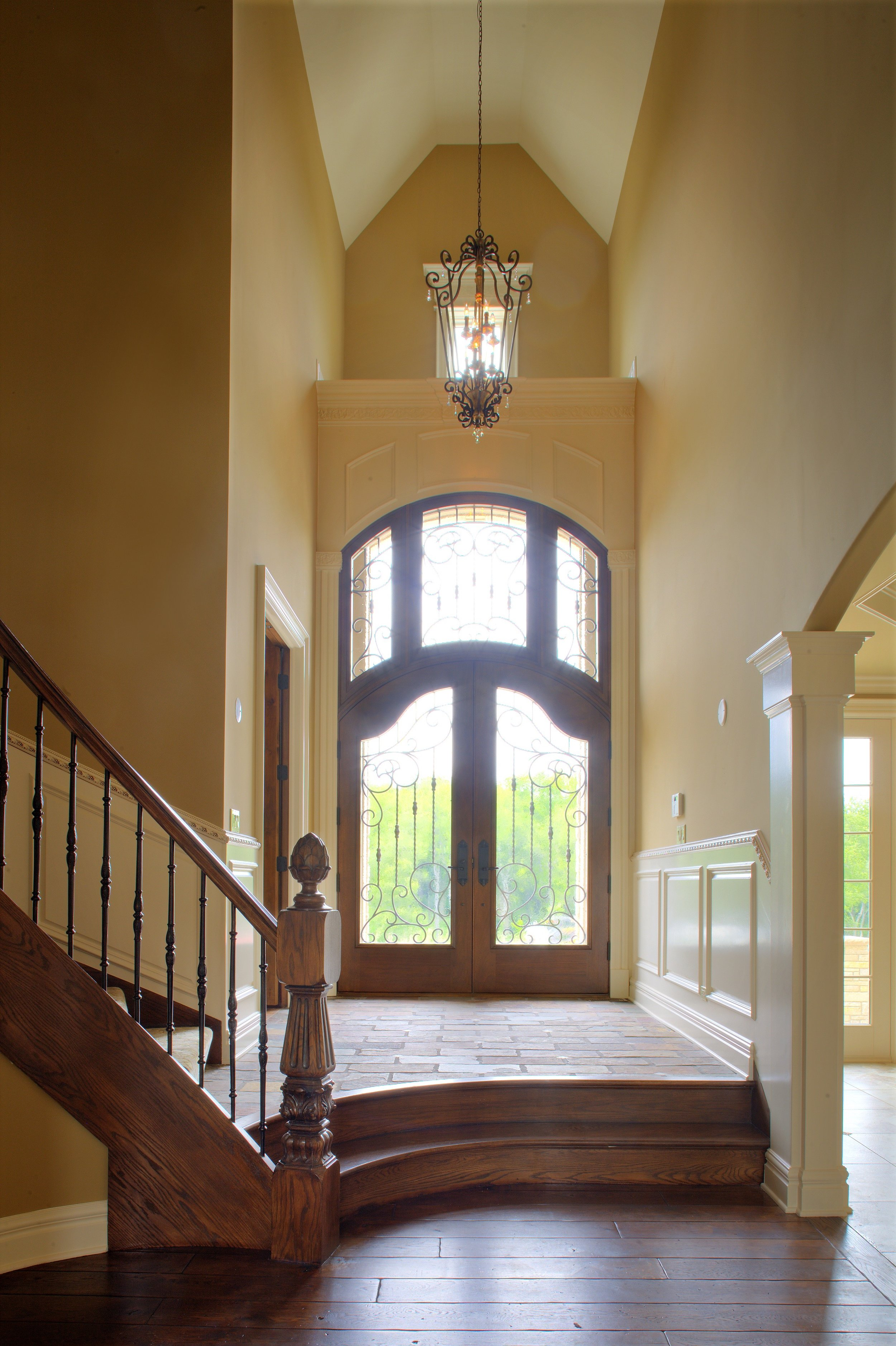 Arched Wooden Front Doors with Arched Transoms and Stained Glass Window in this two and a half Story Naperville IL. Custom Home