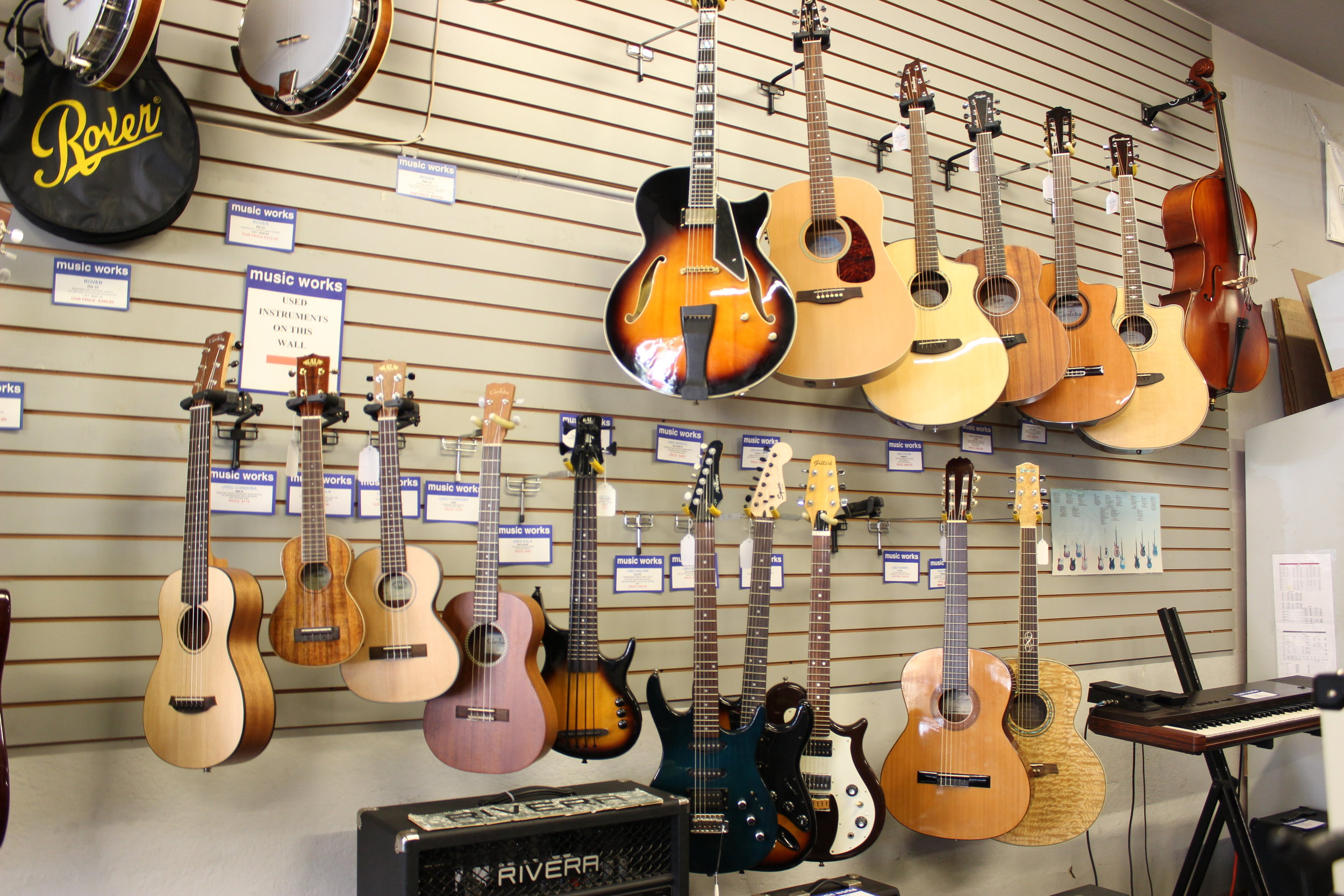 the wall of used equipment  Above is our selection of used instruments including electric guitars, a solid body UBASS, ukuleles, keyboard, steel and nylon string acoustics.