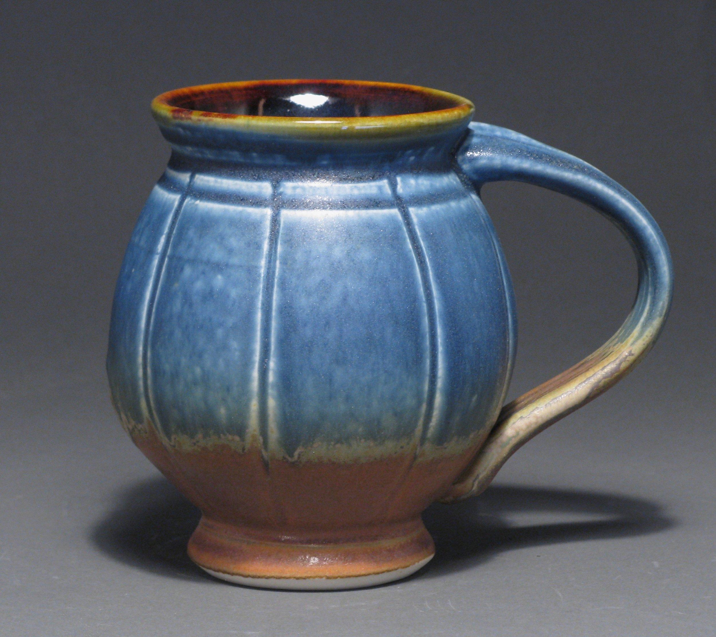 "Round bellied mug  5"" tall  Glazes: matte blue and matte rust"