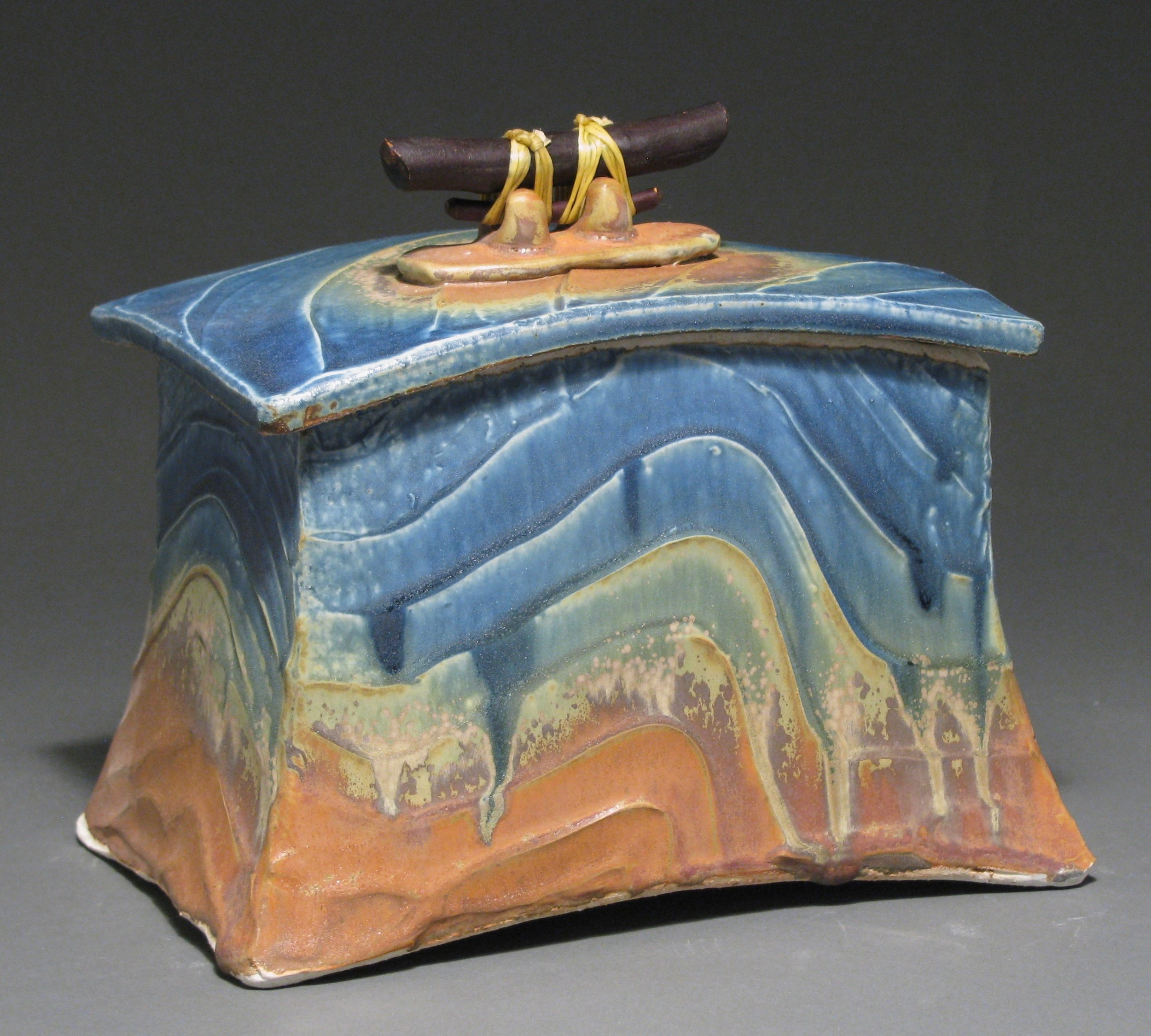 """Lidded box  7"""" tall by 7 3/4"""" long by 5 1/4"""" wide  Glazes: mixed blue and matte rust"""