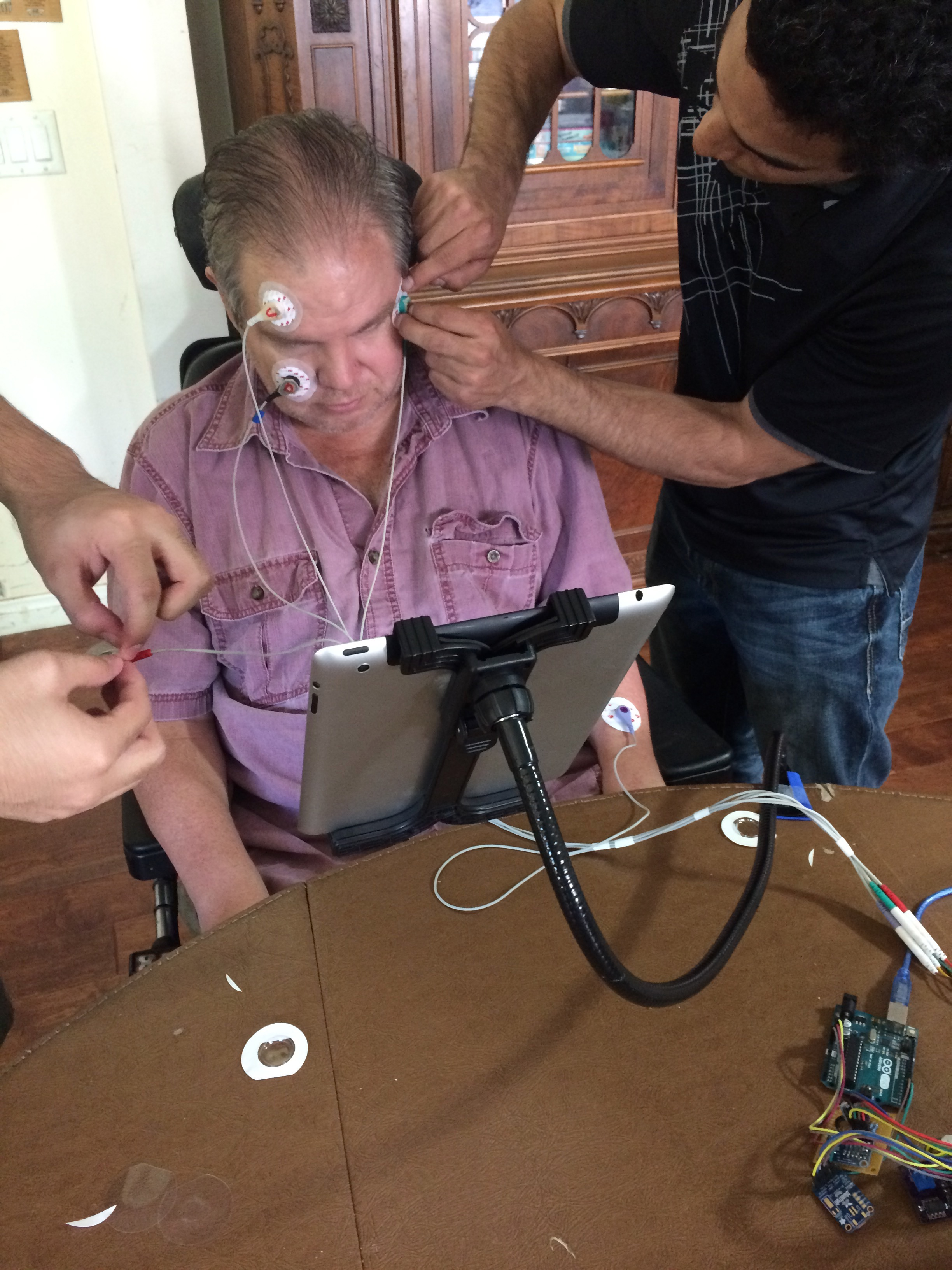 Dominic Nega (left) and Bryce O'Bard attached electrodes to James Blount to test electroocularography equipment. (Photo by Loud Owl)
