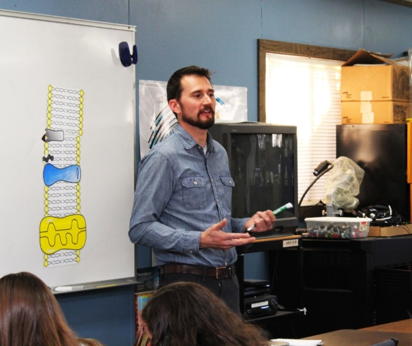 Dr. Bishé explaining an experiment to a classroom of 8th graders.