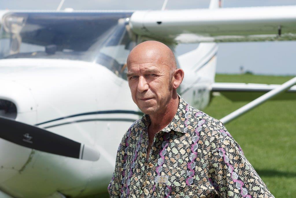 """Max Walch, der mit 17 Jahren das Fliegen begann, ist heute noch deutlich mehr Kilometer in der Luft als im Auto. """"Etwa 20-mal so viel"""", sagt er lachend. Seine Frau fliegt auch und seine Kinder sowieso.  Edle Flieger stehen in der neueren Halle auf dem Rondell, auf dem sie wie auf einem Karussell kreiseln können. Glänzende Doppeldecker in allen Farben und sogar Hubschrauber. """"Es ist viel Arbeit, ein Flugzeug nach dem Fliegen wieder so sauber zu bekommen"""", erklärt Max Walch."""