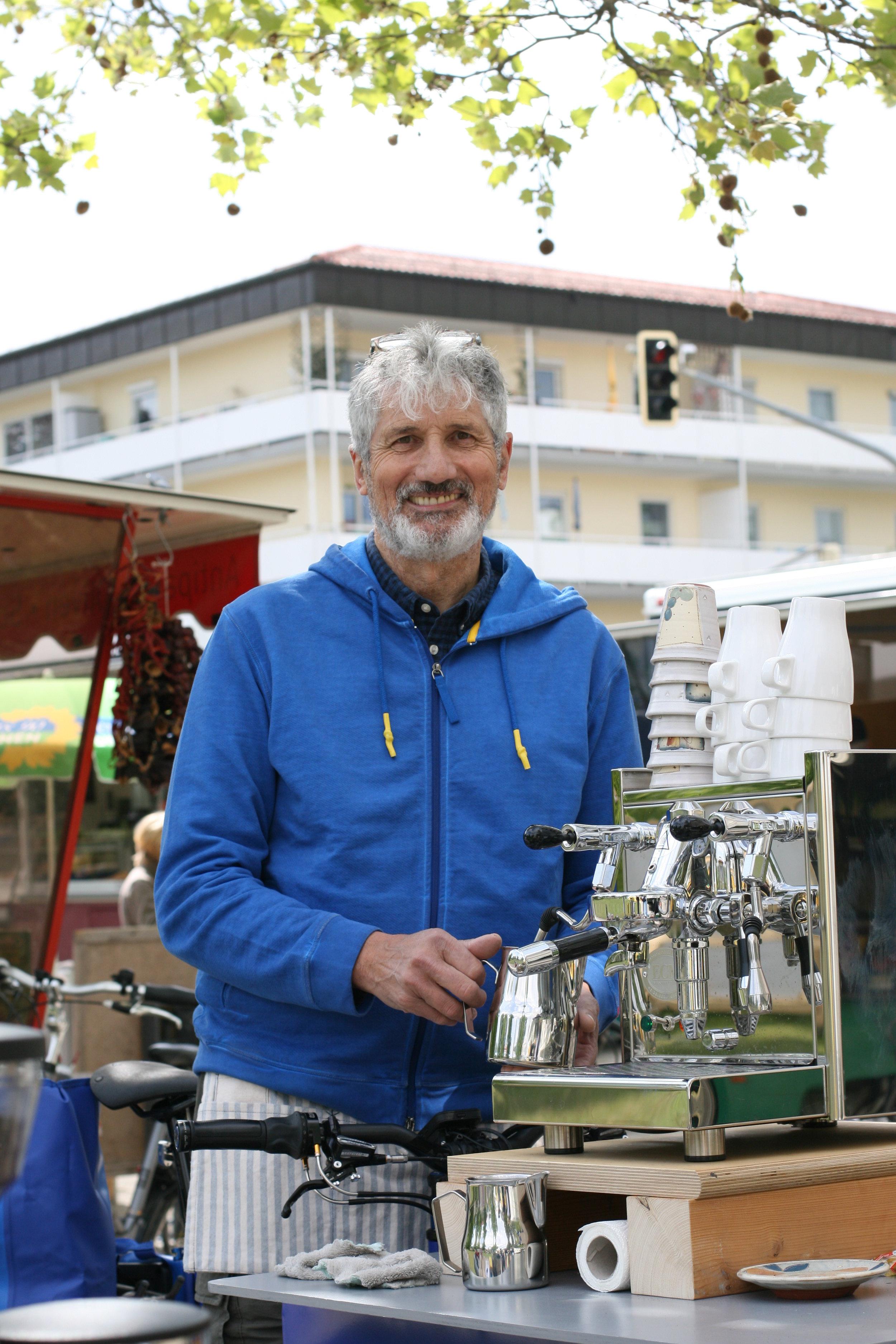 """Thomas Richthammer  Der Kaffee-Radfahrer  Man plaudert, man lacht – stehend, mit einer Tasse duftenden Kaffee in der Hand, mit Bekannten und Unbekannten und mitten auf dem Wochenmarkt in Eichenau. Sich treffen und auch mit Fremden ins Gespräch kommen ist für Thomas Richthammer, geboren im Ruhrpott und Sohn eines Bergmanns, das Normalste von der Welt. Darum freut sich der junggebliebene 66-Jährige auch so über sein gelungenes Projekt: Toms Radbar hat er es genannt und mit der steht er seit dem Frühling auf dem Marktplatz und voraussichtlich noch bei vielen anderen Anlässen auf dem Asphalt. Früher, und das ist erst ein gutes Jahr her, hatte der Eichenauer ein großes Fahrradgeschäft in München. Bevor er in den Ruhestand ging, baute er das E-Lastenfahrrad zu seiner mobilen Kaffeebar um. Unter dem Deckel verbergen sich Kaffeemühle und Maschine. Aufgeklappt wird der Aufbau zur Bar. Ab 7.30 Uhr steht der lustige Barista jetzt auf dem Markt und bringt Menschen bei einer Tasse seines Kaffees zusammen. Seine Rente absitzen, das käme für den aktiven Sportler, der sich auch im Asylhelferkreis engagiert, Spanisch lernt und zweimal in der Woche den Pausenverkauf in der Realschule Puchheim abwickelt, ja gar nicht in Frage. Verschmitzt funkeln seine Augen: """"Und ich habe noch ganz viele weiteren Ideen."""""""