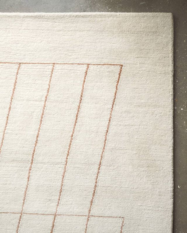 Pale terracotta lines descend in a close-up of our Amai rug. Handmade to order.  Lead time 8-12 weeks. Initialled with an 'A' woven into the bottom-left corner. Hand-knotted in Nepal from 100% Tibetan wool. Size approx 260 x 180cm. Numbered edition of 100. Certified by GoodWeave.