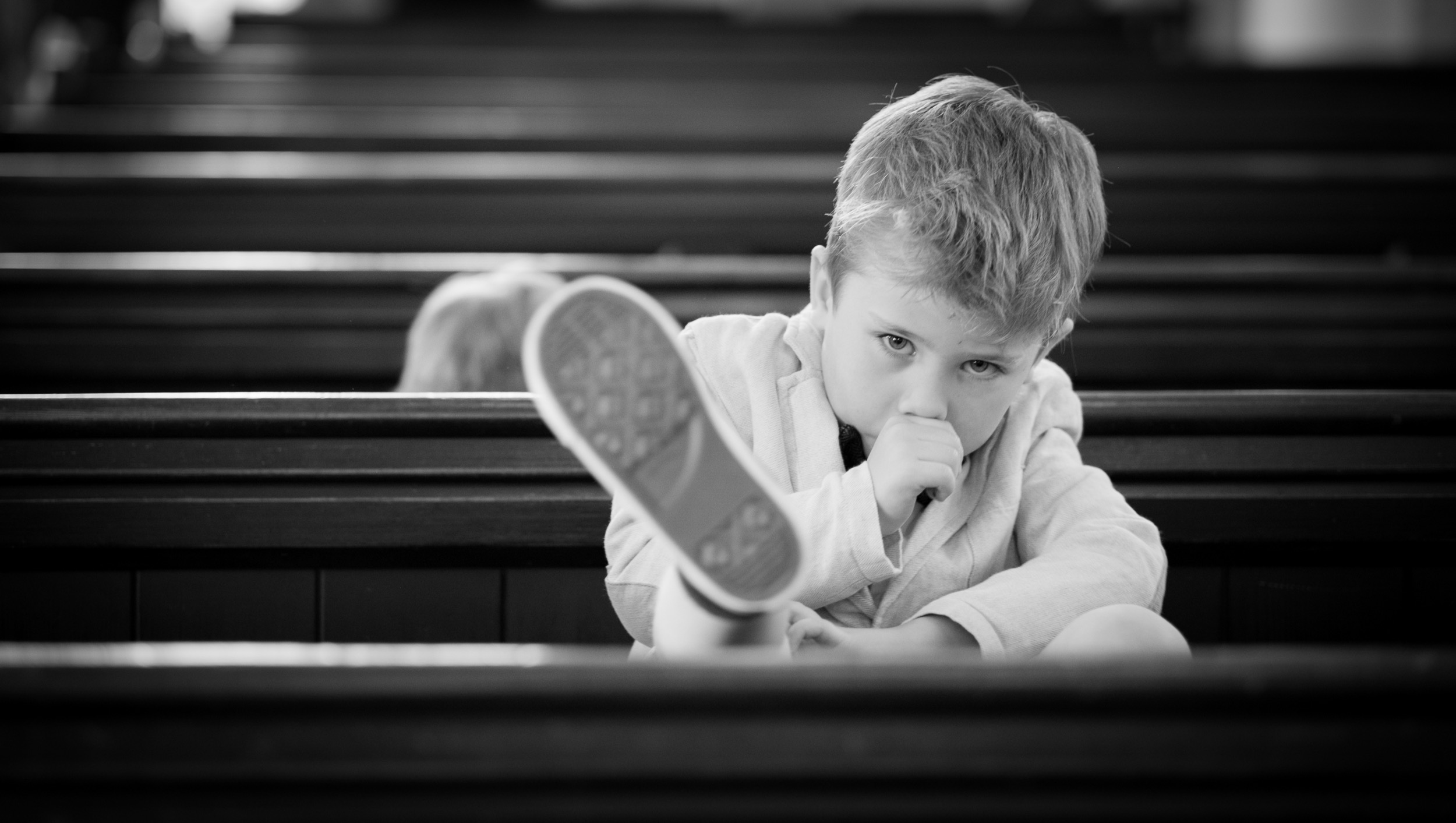Amusing young man or boy in the church looking bored and grumpy waiting for the wedding to start