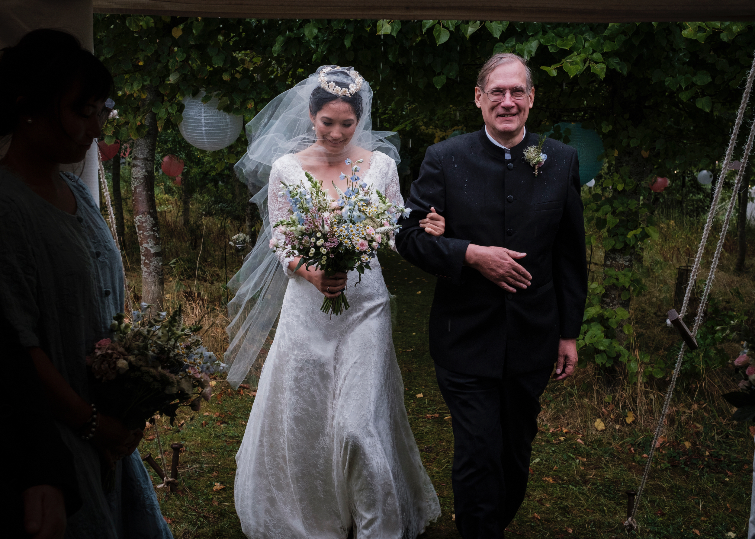 APhotograph from a country wedding in Gloucestershire of a bride walking down the aisle with her father in the rain