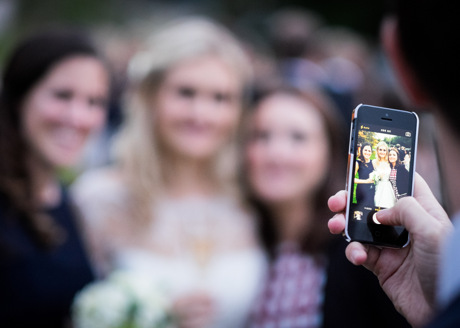 Guest taking a wedding photograph on a smart phone