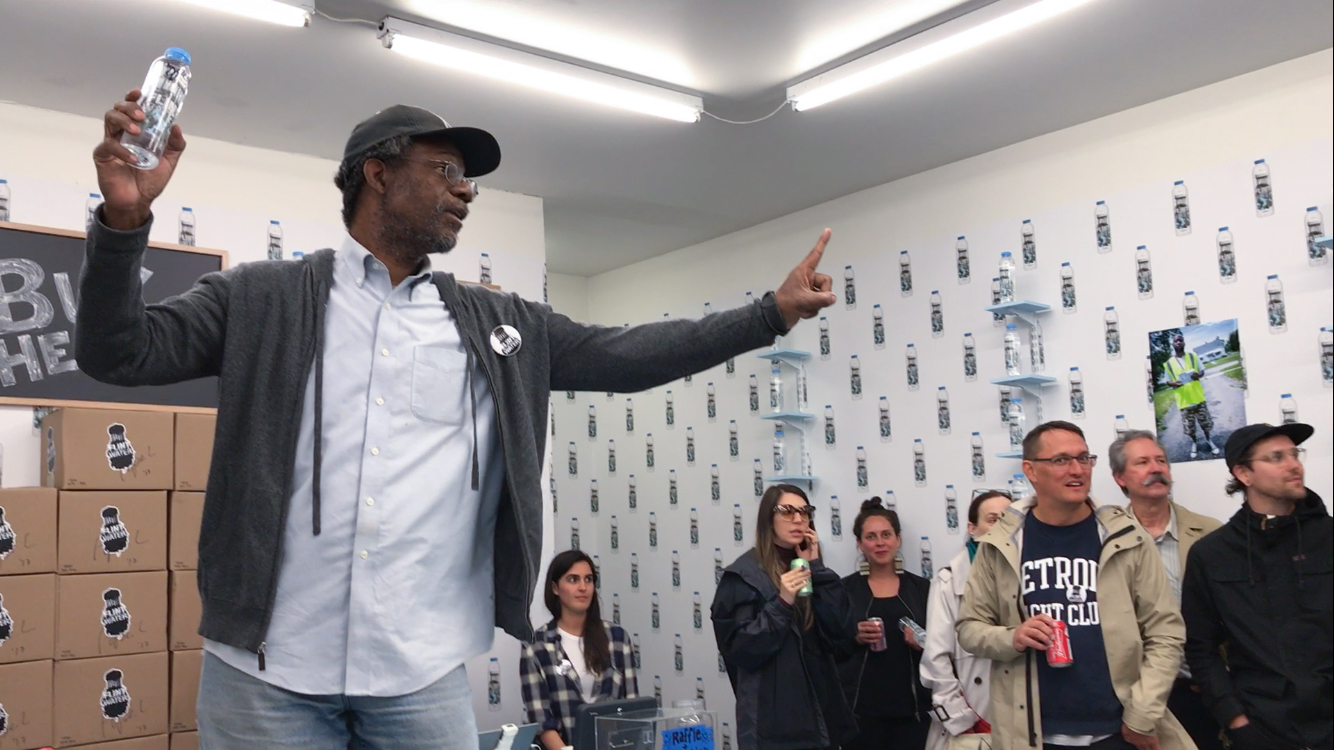 Pope.L auctions a bottle of Flint Water signed by the artist during the opening of Flint Water, September 7, 2017 at What Pipeline, Detroit. Courtesy the Artist and What Pipeline.© Pope.L  Homepage image: Pope.L, Flint Water Single Unsigned Bottle ,2017. 16 oz. plastic bottle of contaminated water obtained from Flint, MI. Courtesy the artist and What Pipeline.© Pope.L