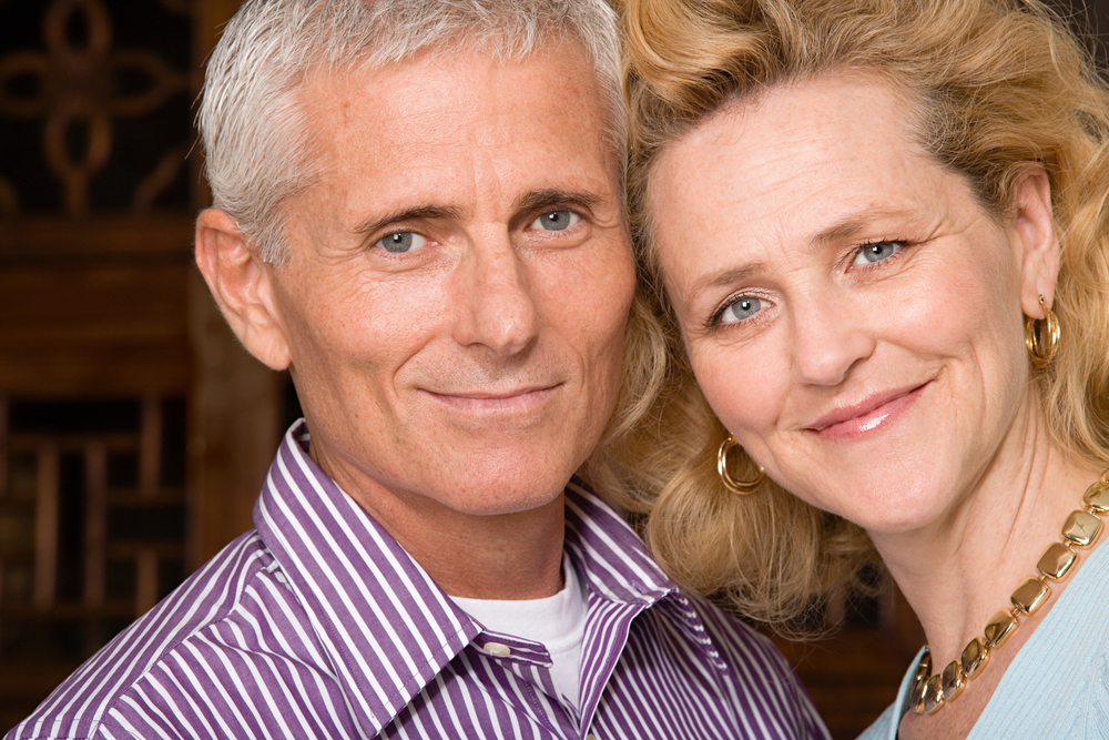 stock-photo-portrait-of-a-happy-mature-couple-over-a-gray-background-134273450.jpg