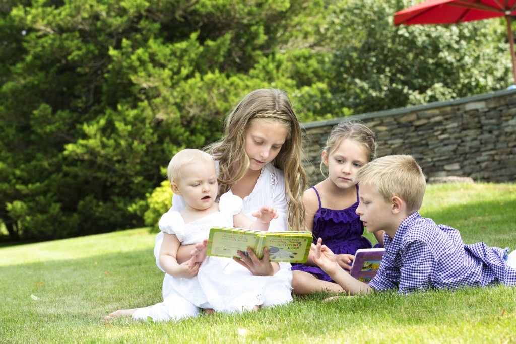 Siblings reading a book to their younger sister at their home photo shoot
