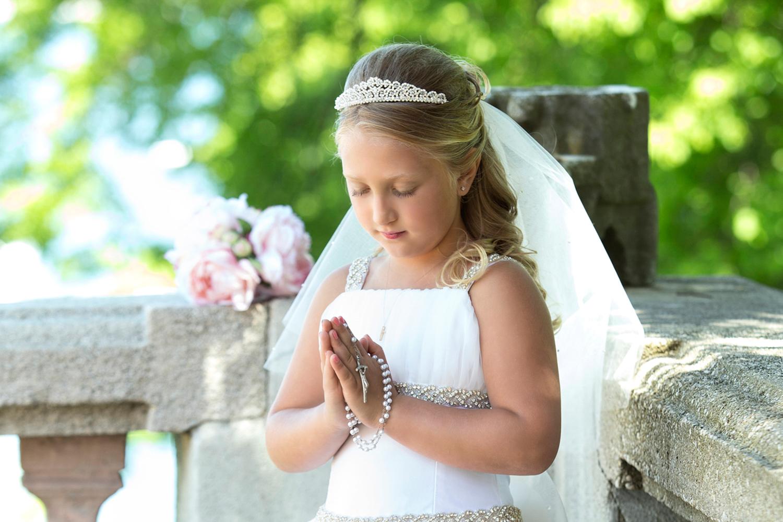 Photographer capturing Communion girl praying at the Vanderbilt Museum Centerport NY