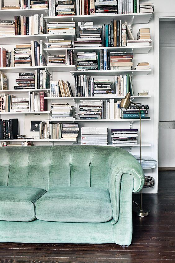 Full bookshelf behind green sofa