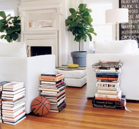 Books stacked next to furniture in living room