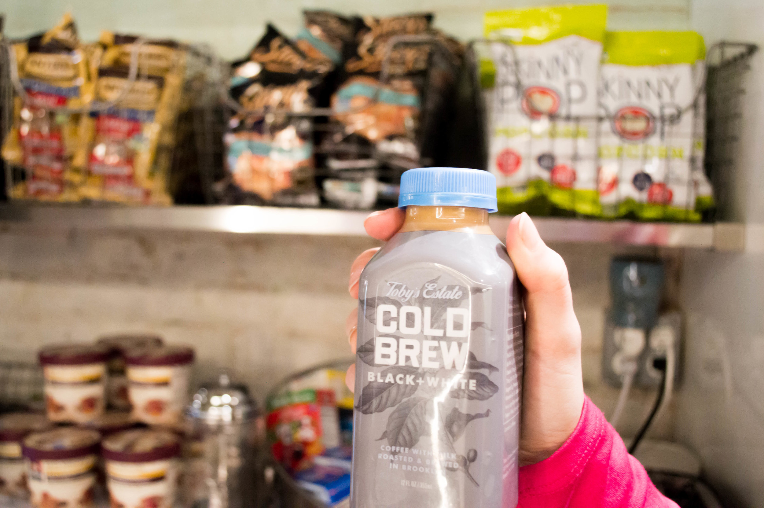 Bottle of cold brew coffee being held up in front of shelves of snacks
