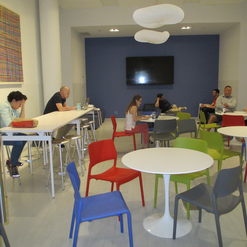 Engaging spaces, such as a colorful cafe at Civic Hall, encourage collaboration and cross-pollination across disciplines while providing an alternative workspace for untethered knowledge workers.