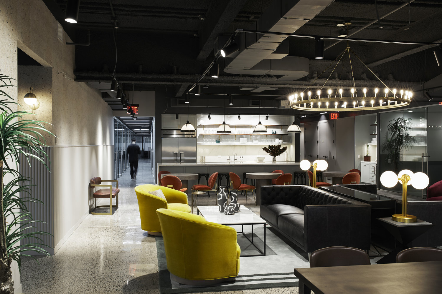Modern office space lounge area with black sofa and yellow chairs