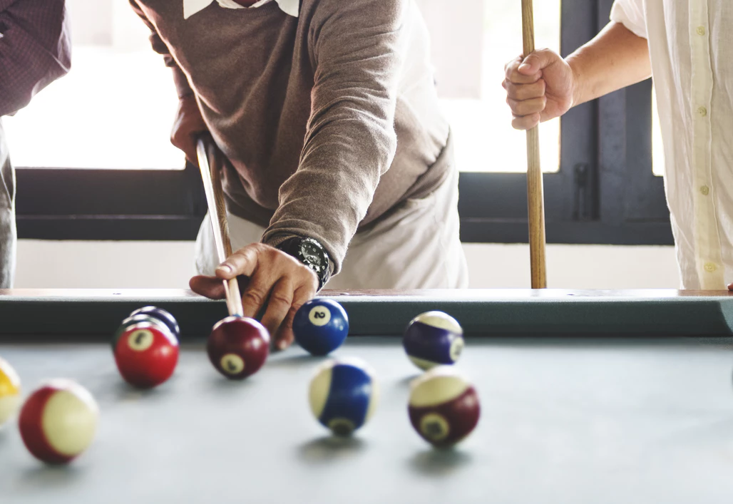 Coworkers playing pool to motivate employees by having fun
