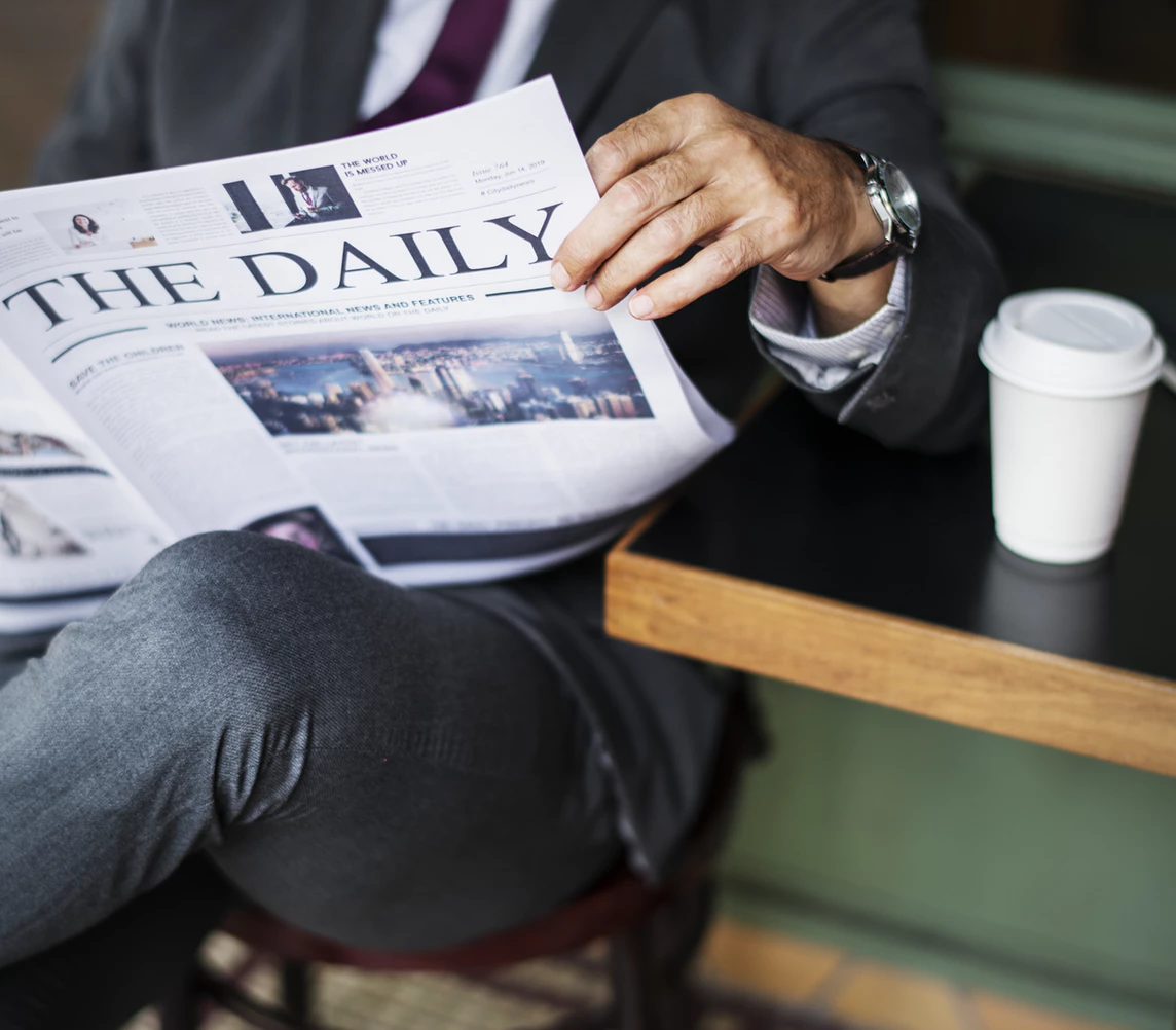 Man reading a newspaper at a coffee shop