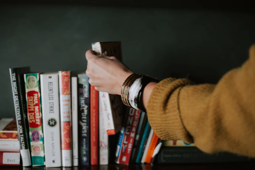 Woman's arm reaching for a book on a shelf of books