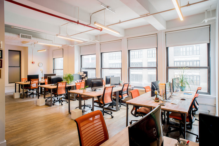 coworking space with desks, chairs, and computers