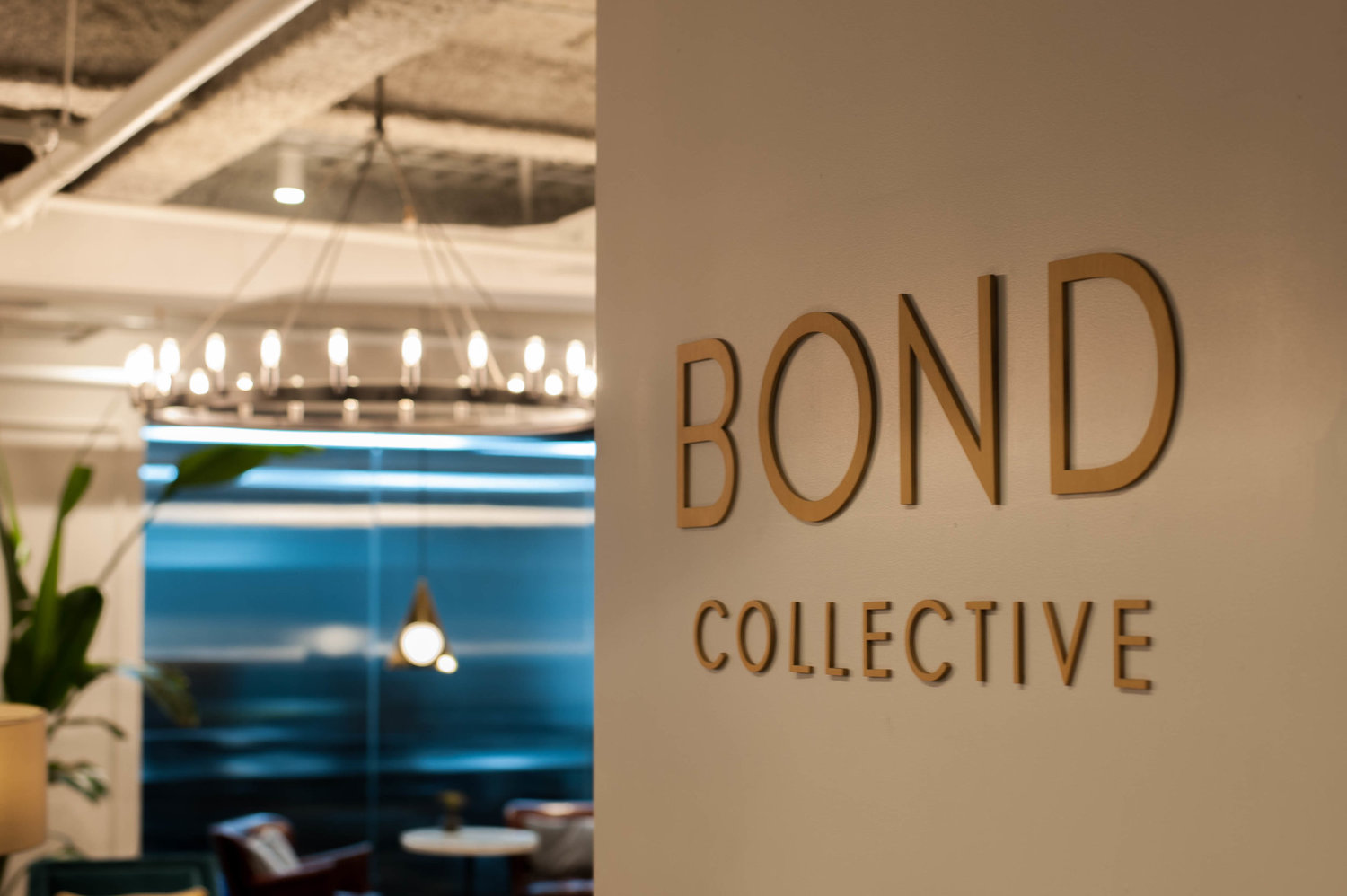 open area at shared office space with Bond Collective branding on the wall