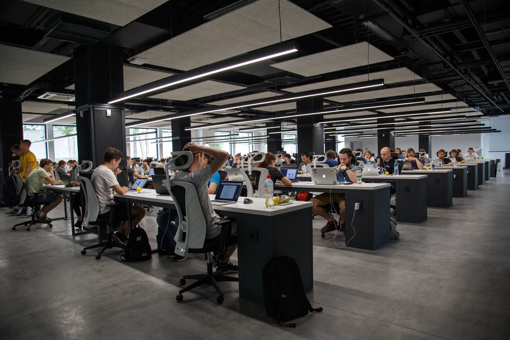 large open room with people working on computers at desks