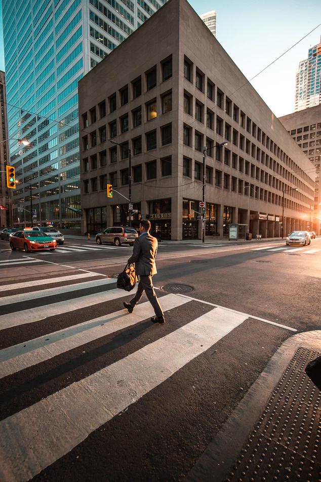 businessman crossing busy street in crosswalk