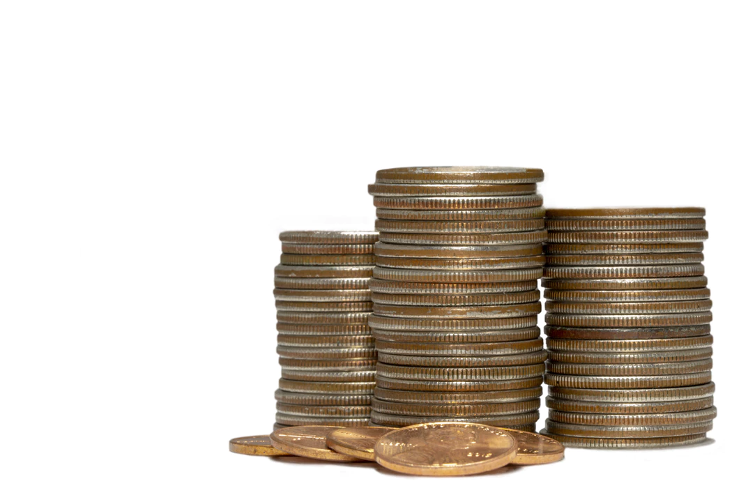 stacks of quarters next to a few pennies on white background