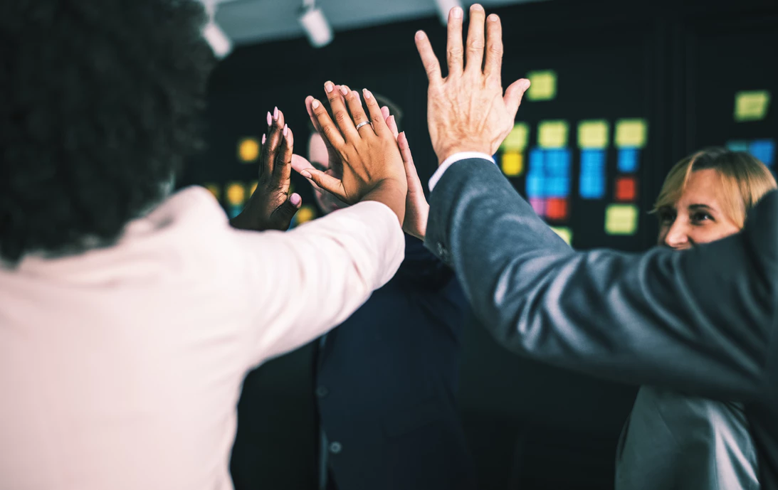 business teammates celebrating with high fives in an office area