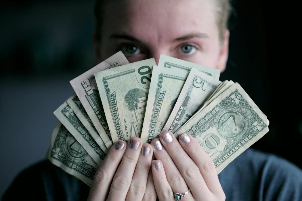 woman holding fanned out cash in front of her face