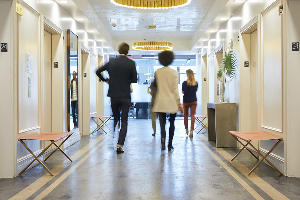 businesspeople walking down white hallway with several elevators