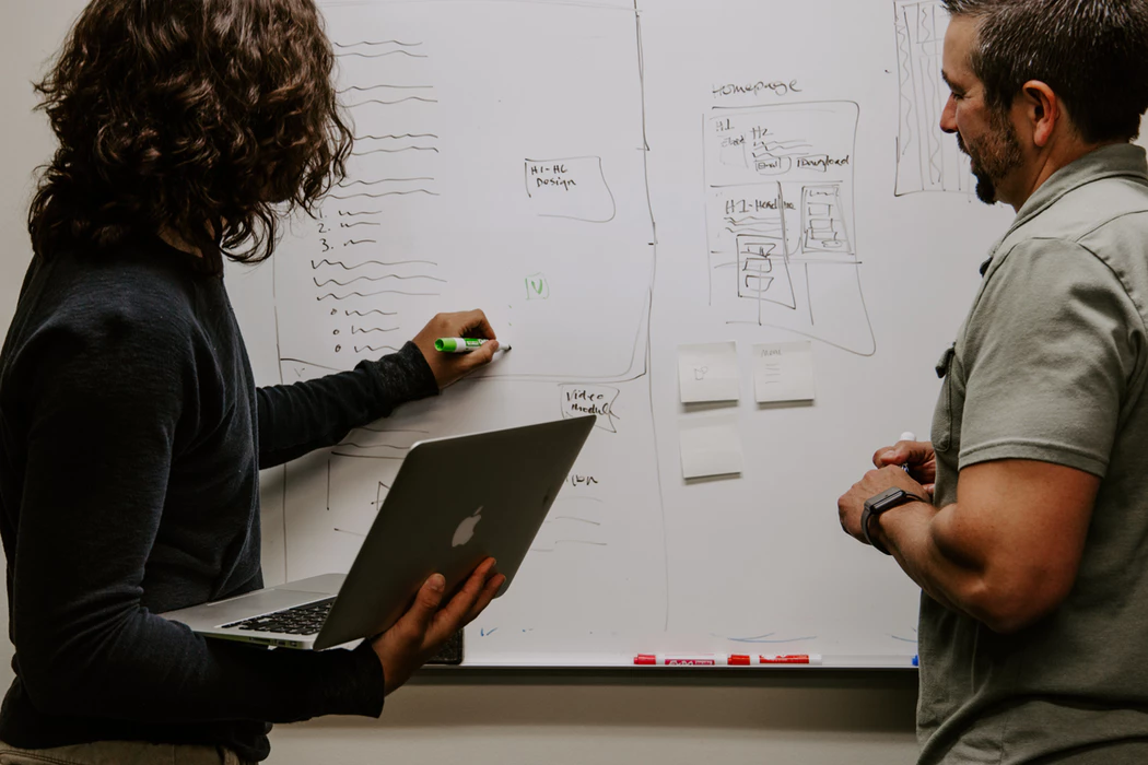 man and woman strategizing about startup funding in front of a dry erase board